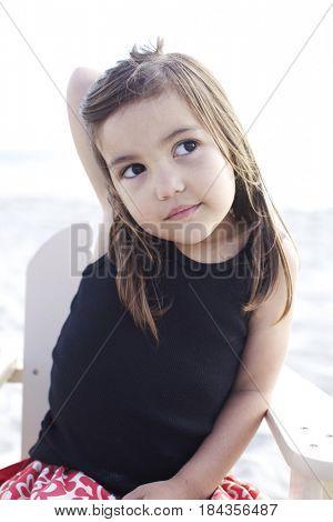 Serious Hispanic girl sitting on beach