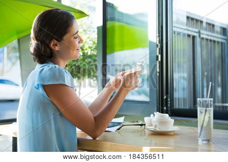 Smiling female executive using mobile phone in café