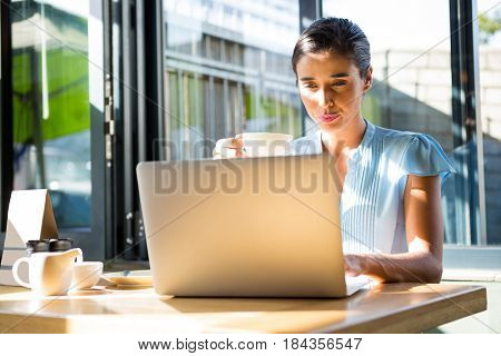 Focused female executive working on laptop in café