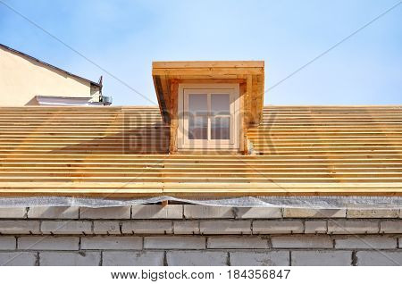 The process of construction a wooden roof system with a square dormer window.