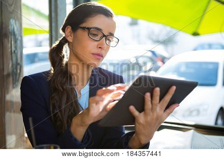 Business executive sitting and using digital tablet in café