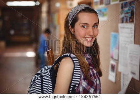 Portrait of smiling schoolgirl standing near notice board in corridor at school