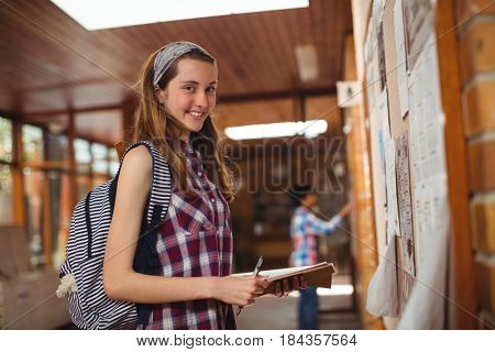Portrait of smiling schoolgirl standing with book near notice board in corridor at school