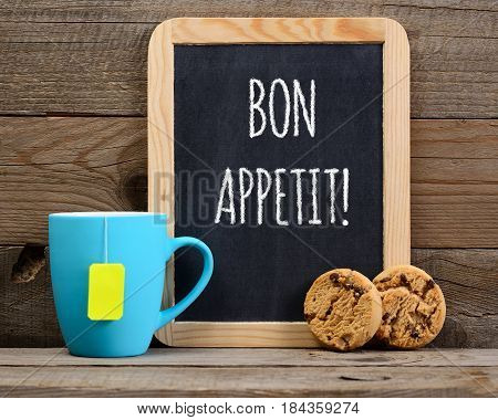 Tea cookies and blackboard with Bon appetit wishes on wooden background