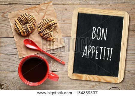 Wishes bon appetit on small blackboard coffee cup and cookies on wooden table
