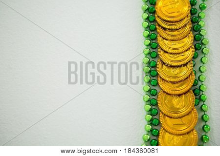 St Patricks Day gold chocolate coin and beads on white background