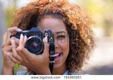 Woman taking picture with digital camera in park
