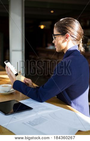 Side view of business executive using mobile phone in café