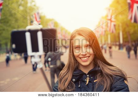 London travel selfie young woman. Joyful brunette girl smilling at camera with long tree alley leading to Buckingham Palace. Modern travelling