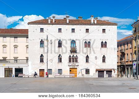 Udine - May 2016, Friuli-Venezia Giulia region, Italy: Typical Italian house in Venetian style on the square of Udine in sunny day with blue sky