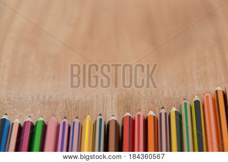 Colorful color pencil arranged in diagonal line on wooden background