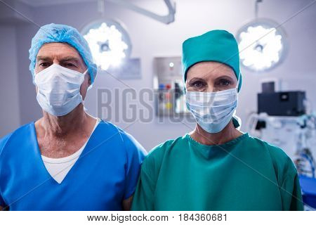 Portrait of surgeons wearing surgical mask in operation theater of hospital