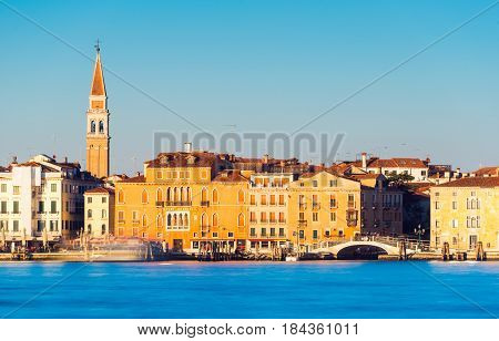 Venice - January 2017, Italy: Cityscape during the sunset, old historical buildings and bell tower rises over the city, long exposure photography