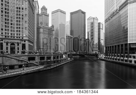 Chicago - March 2017, IL, USA: Black and white photo of Chicago downtown with skyscrapers, hotels, promenade and river viewed from the bridge, long exposure photography