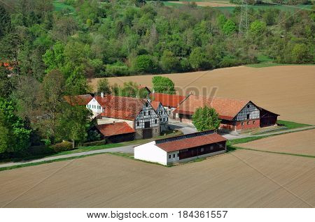 Half-timbered outbuildings in the middle of agricultural earthy field in Germany.