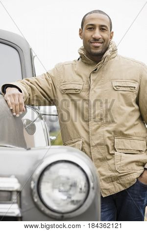 African American man standing next to old-fashioned truck