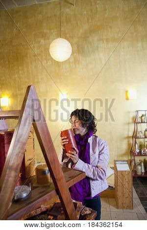 Ecuadorian woman smelling candle in shop