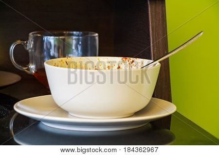 Close up image of dirty dishes bowl on plate with spoon in it