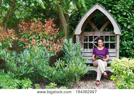 Mixed race woman reading magazine in backyard