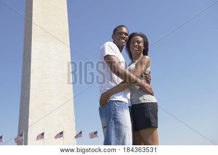 African American couple hugging near monument