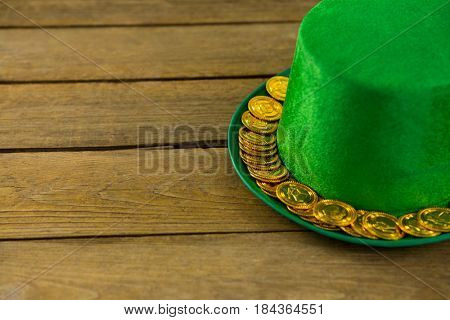 St Patricks Day leprechaun hat with gold chocolate gold coins on wooden background