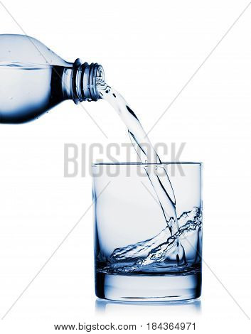 Water pouring into wide glass from bottle isolated on white background