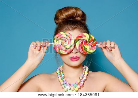 Portrait Of A Beautiful Young Woman With Candy On A Blue Background. The Blonde With The Colored Can