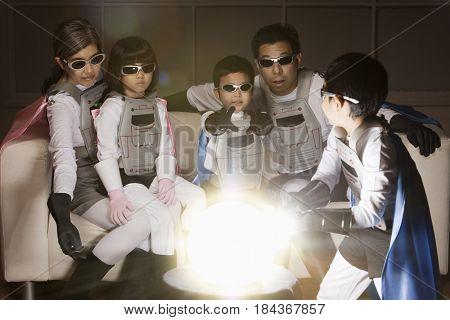 Asian superhero family watching glowing orb
