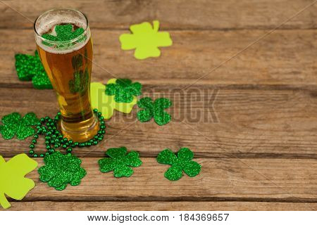 Glass of beer, beads and shamrock for St Patricks Day on wooden table