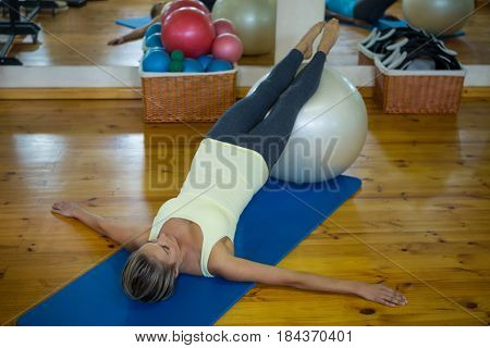 Woman exercising on fitness ball in gym