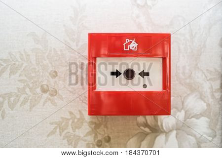 Closeup of red fire alarm box with black button on beige wall background