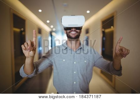 Male executive using virtual reality headset in corridor at office