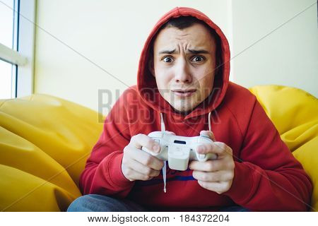 Emotional teenager playing home games console using a gamepad. Video games in his spare time. Looking into the camera