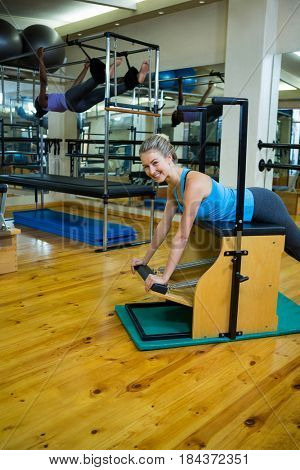 Portrait of beautiful woman exercising on wunda chair in gym
