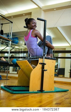 Portrait of happy woman exercising on wunda chair in gym