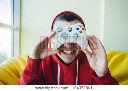A young man demonstrates a joystick for video game holding at eye level. The concept of video games