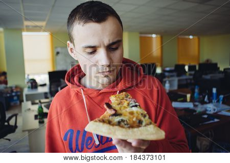 The young man eating delicious pizza against a background of office space. Fast food a break at work.