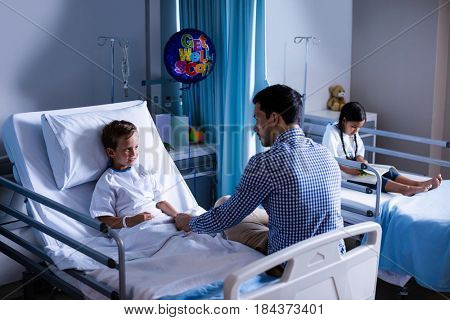 Father consoling his son during visit in ward at hospital