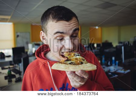 A young office worker eating delicious pizza against a background of office space. Fast food a break at work.
