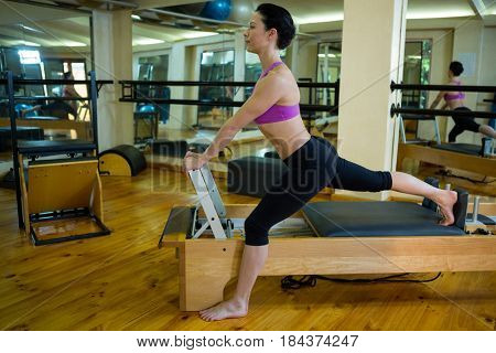 Determined woman performing stretching exercise on reformer in gym