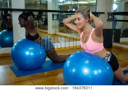Two smiling women performing pilate on exercise ball in fitness studio