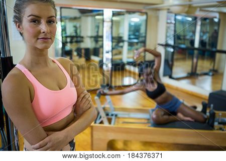 Portrait of smiling fit woman standing with arms crossed in fitness studio