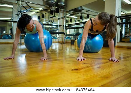 Women interacting while exercising on fitness ball in gym