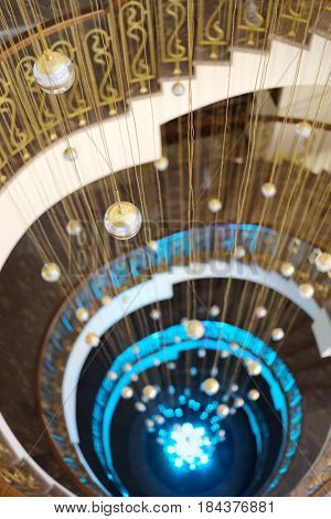 Beautiful empty spiral staircase with illumination and hanging balls in hotel