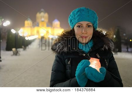 Woman smiles and holds burning candle in glass pot, Cathedral of Gregory Enlightener with illumination out of fcous, Yerevan, Armenia