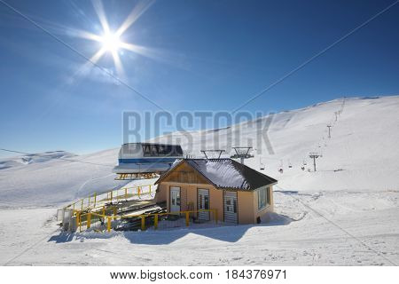 Small cottage. sun and modern ropeway in snowy mountains at winter day