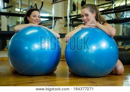 Portrait of happy women leaning on fitness ball in gym