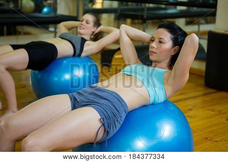 Determined women exercising on fitness ball in gym