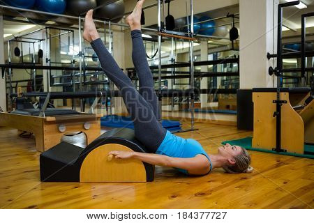 Fit woman doing pilates on arc barrel in fitness studio