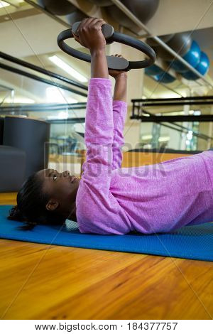 Fit woman exercising with pilates ring on mat in fitness studio